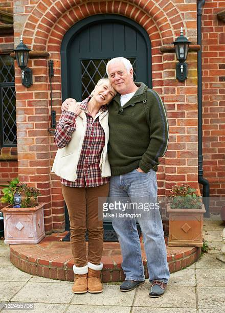 Retired couple embracing outside house