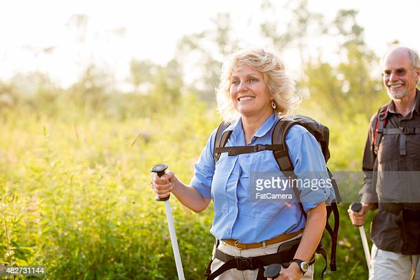 retired couple enjoying nature - green shorts stock photos and pictures