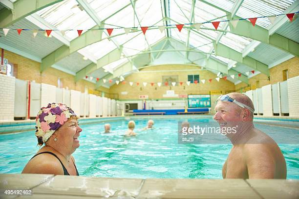 retired couple having fun at the swimming pool - swimming stock pictures, royalty-free photos & images