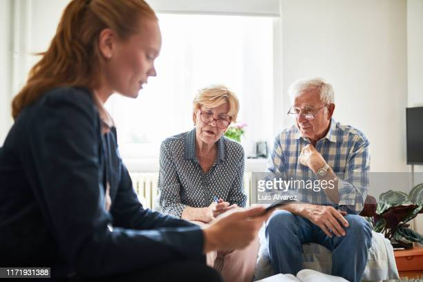 retired couple in meeting with a financial advisor at home - german short haired pointer stock pictures, royalty-free photos & images