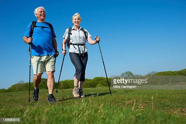 Retired Couple Nordic Walking Through Hills