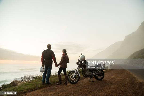 retired couple on a motorbike ride on a coastal road - motorcycle stock pictures, royalty-free photos & images