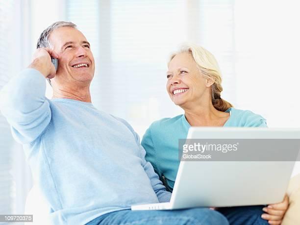 couple de retraités à l'aide d'ordinateur portable avec un homme sur téléphone portable