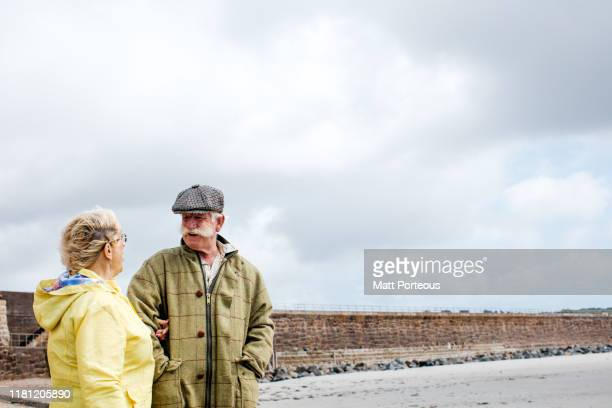 retired couple walking on beach - two people stock pictures, royalty-free photos & images