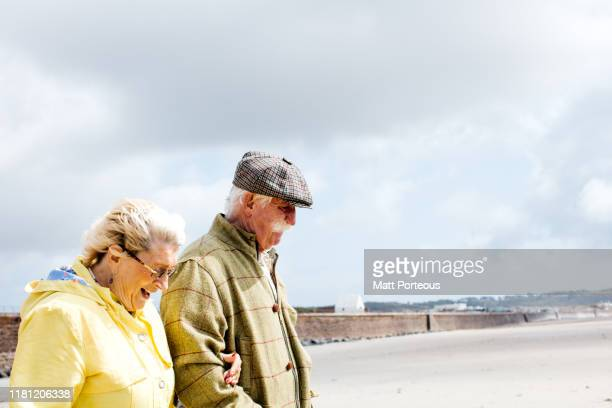 retired couple walking on beach - real people stock pictures, royalty-free photos & images