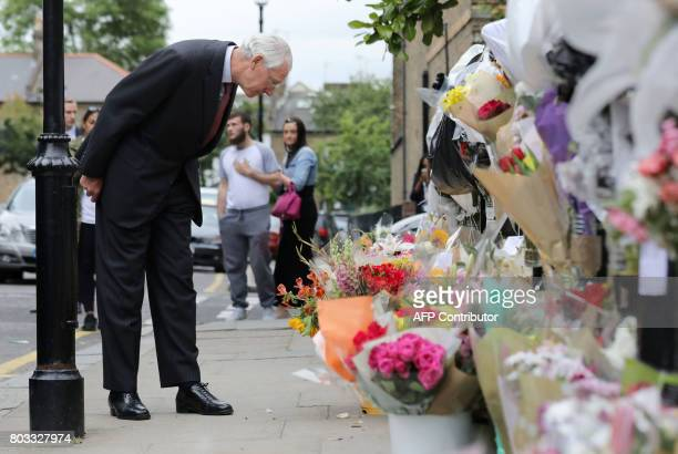 Retired Court of Appeal judge Sir Martin MooreBick who will lead the Grenfell Tower fire public inquiry looks at flowers left in tribute to the...