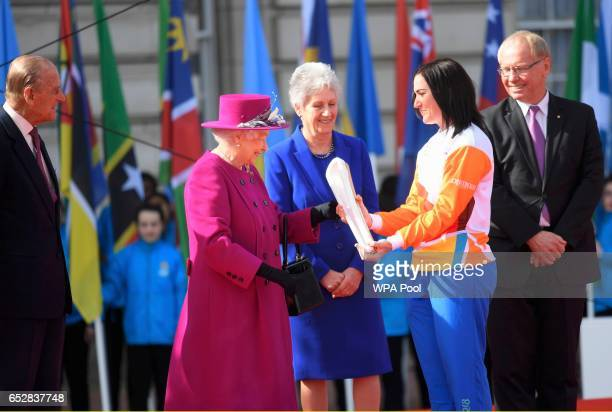 Retired cyclist Anna Mears from Australia receives the baton from Queen Elizabeth during the launch of The Queen's Baton Relay for the XXI...