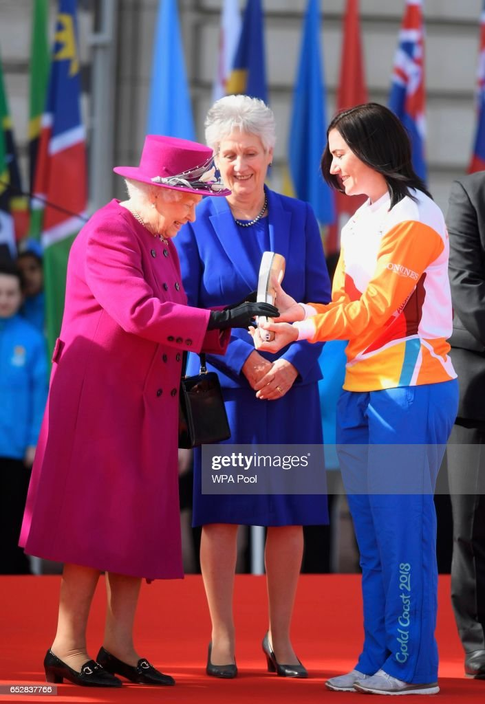 Retired cyclist Anna Mears from Australia receives the baton from Queen Elizabeth during the launch of The Queen's Baton Relay for the XXI Commonwealth Games being held on the Gold Coast in 2018 at Buckingham Palace on March 13, 2017 in London, United Kingdom.
