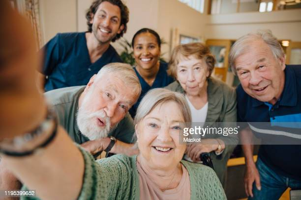 retired elderly woman taking selfie with friends and caregivers at retirement home - medium group of people stock pictures, royalty-free photos & images