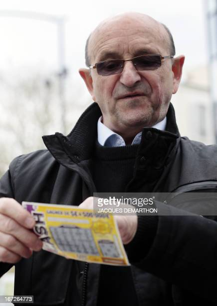 Retired engineer Robert Riblet holds a scratchcard by French state gaming company La Francaise des Jeux on April 23 2013 in BoulogneBillancourt FDJ...