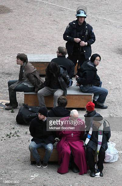 Retired Episcopal Bishop George E. Packard along with Occupy Wall Street activists sit on benches after being arrested after gaining entrance to the...