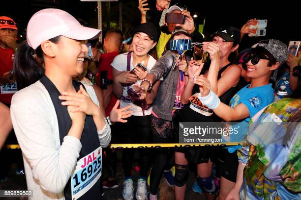 Retired figure skater and former Olympian Mao Asada celebrates with fans before the start of the Honolulu Marathon 2017 on December 10 2017 in...