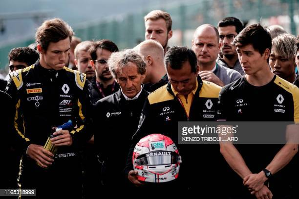 Retired French racing driver and Renault special advisor Alain Prost and Renault team members observe a minute's silence before the start of the race...