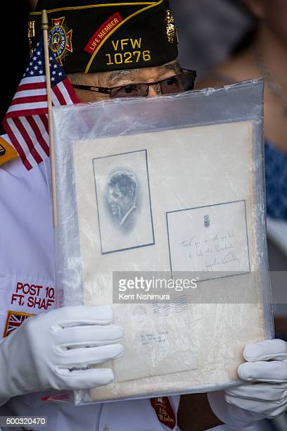 Retired Gunnery Sgt Robert I Hashida holds up a letter as the USS Preble performs a passinreview during a memorial service marking the 74th...