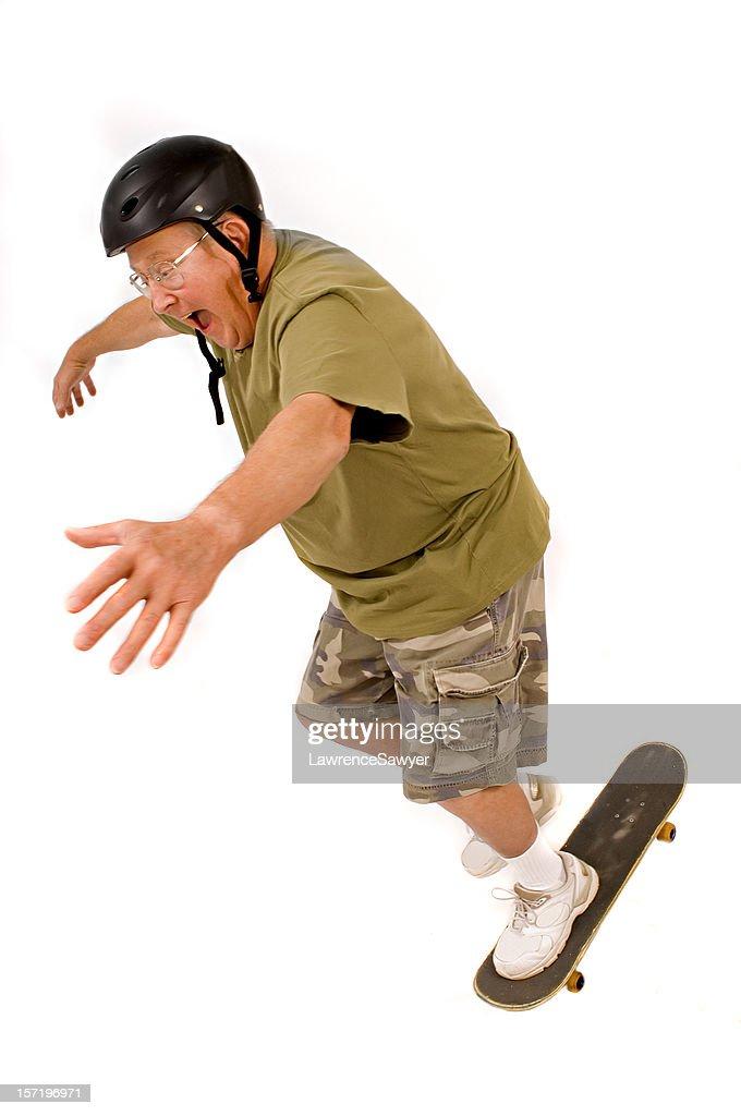 retired guy falls off his skateboard : Stock Photo
