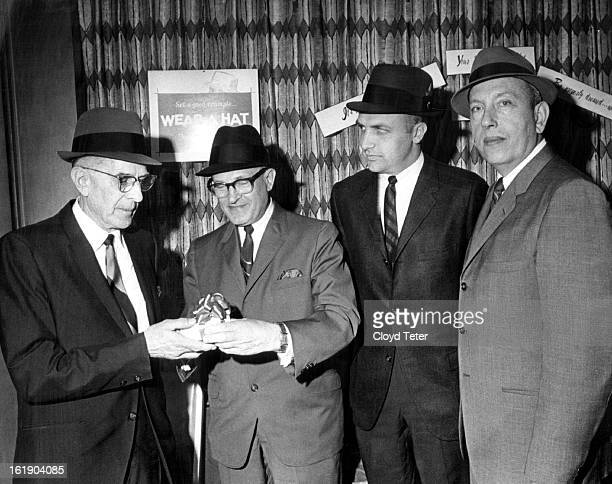 FEB 10 1966 Retired Hat Seller Gets Gift Vic Elliott left who has retired after 48 years in the hat department at Gano Downs Co receive a gift clock...