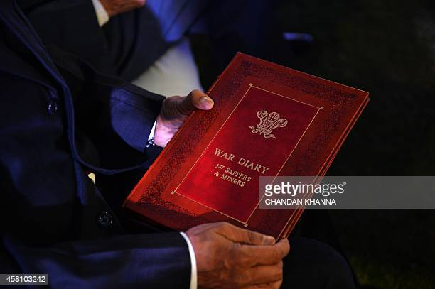 A retired Indian soldier holds a Regimental War Diary during a WWI commemoration event in New Delhi on October 30 2014 British defence minister...