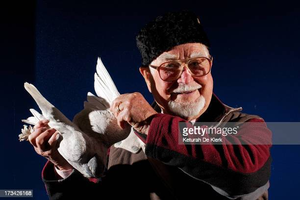 Retired international pigeon judge Jules de Brenni holds a pigeon at the 2013 Australian National Pigeon Show at the Adelaide Showground on July 12...