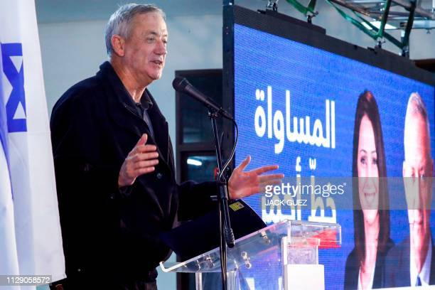 Retired Israeli army general Benny Gantz one of the leaders of the Blue and White political alliance speaks next to a large screen depicting his face...