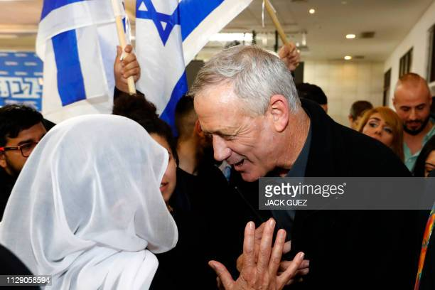 Retired Israeli army general Benny Gantz , one of the leaders of the Blue and White political alliance, speaks to a woman wearing a white veil during...