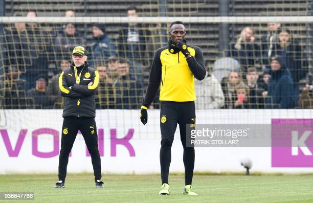 TOPSHOT Retired Jamaican Olympic and World champion sprinter Usain Bolt stands next to Borussia Dortmund's head coach Peter Stoeger as he takes part...