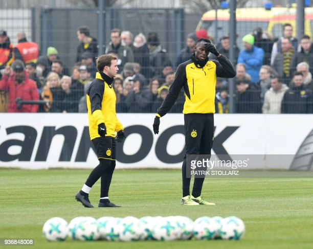 Retired Jamaican Olympic and World champion sprinter Usain Bolt stands next to Borussia Dortmund's midfielder Mario Goetze as he takes part in a...