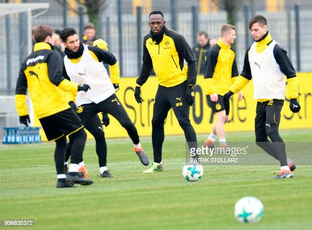 Retired Jamaican Olympic and World champion sprinter Usain Bolt plays the ball as he takes part in a training session of German first Bundesliga...