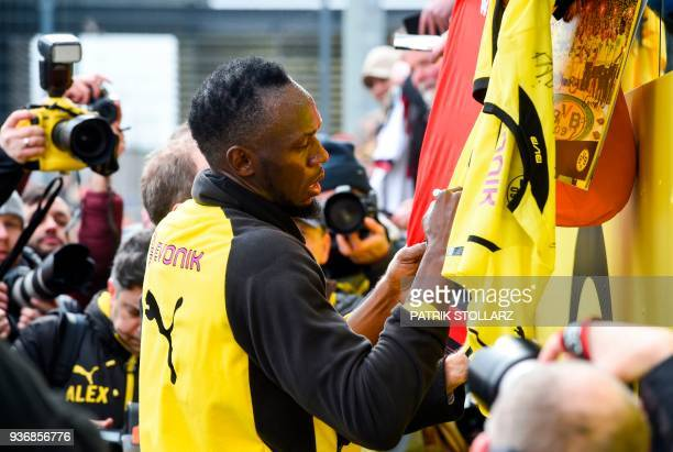 Retired Jamaican Olympic and World champion sprinter Usain Bolt signs autographs on tshirts after he took part in a training session of German first...