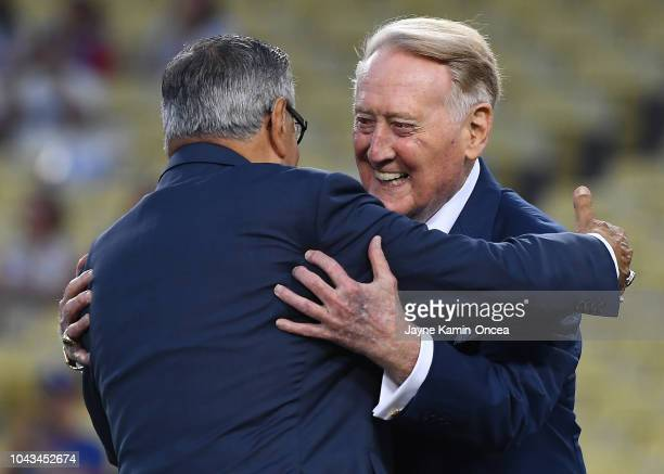 Retired Los Angeles Dodgers broadcaster Vin Scully right hugs Los Angeles Dodgers Spanish language broadcaster Jaime Jarrin during a pregame ceremony...