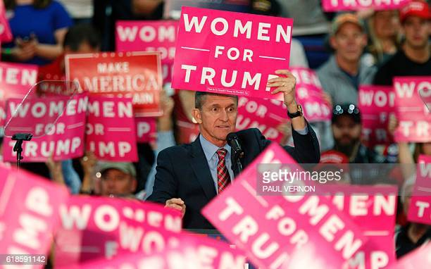 Retired Lt General Michael Flynn holds up a sign while speaking to the crowd gathered to see US Republican presidential candidate Donald Trump at The...