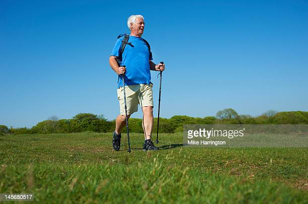 Retired Male Nordic Walking in Countryside
