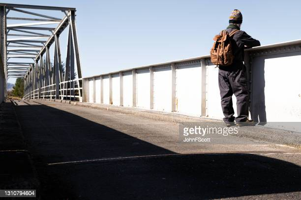 retired man checking the view from a steel bridge - johnfscott stock pictures, royalty-free photos & images