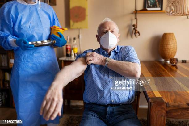 retired man getting ready covid-19 vaccination at home - long sleeved stock pictures, royalty-free photos & images