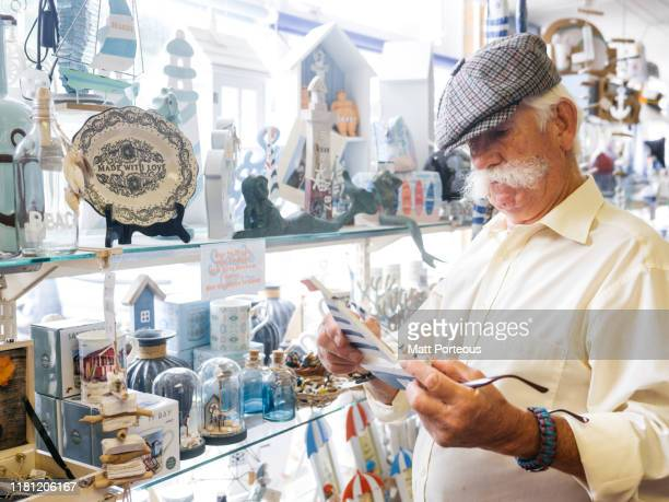 retired man in seaside gift shop - gift shop stock pictures, royalty-free photos & images