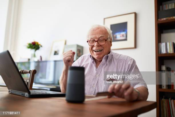 retired man purchasing online using wireless devices - only senior men stock pictures, royalty-free photos & images