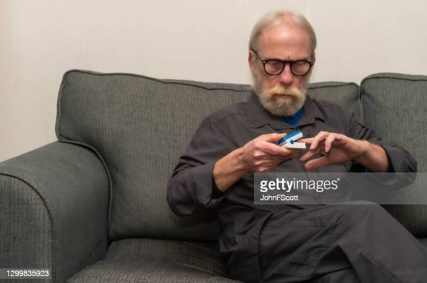 retired man putting an oximeter onto his finger to check the oxygen level in his blood - johnfscott stock pictures, royalty-free photos & images