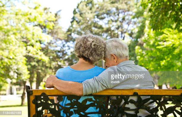 retired man sitting with arm around woman on bench - retirement community stock pictures, royalty-free photos & images