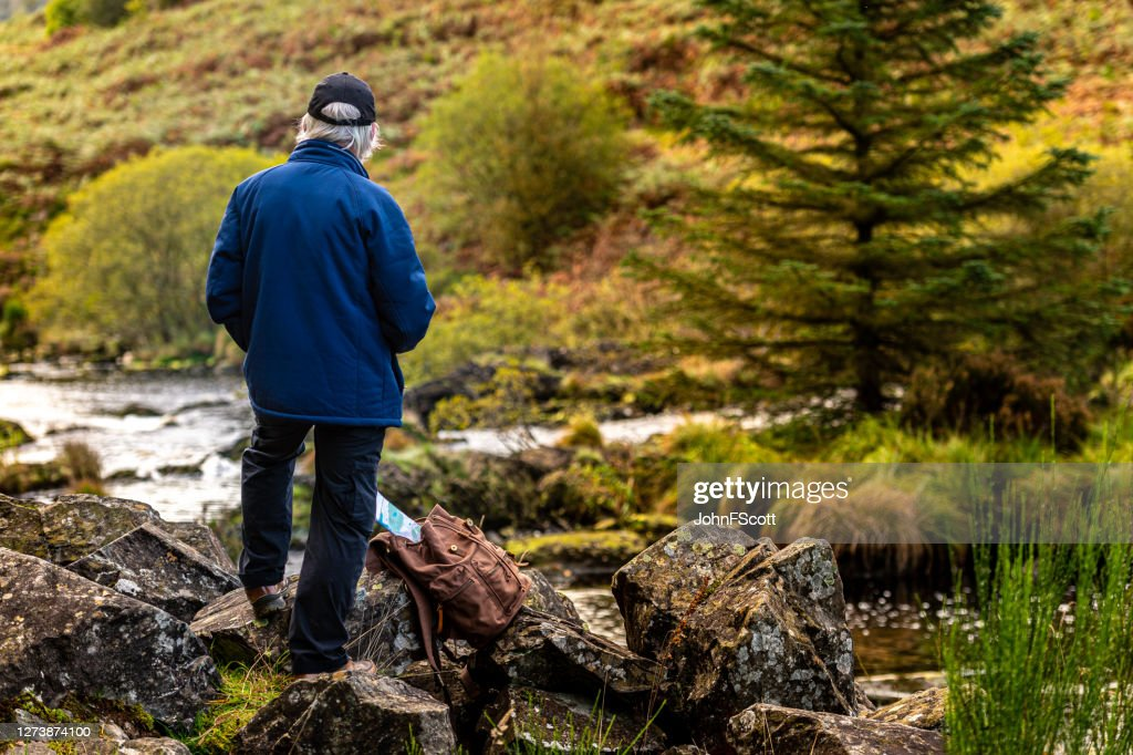 Retired man standing alone on a rock beside a Scottish river in rural south west Scotland. : Stock Photo