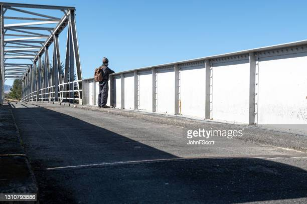 retired man stopping to look from a steel bridge - johnfscott stock pictures, royalty-free photos & images