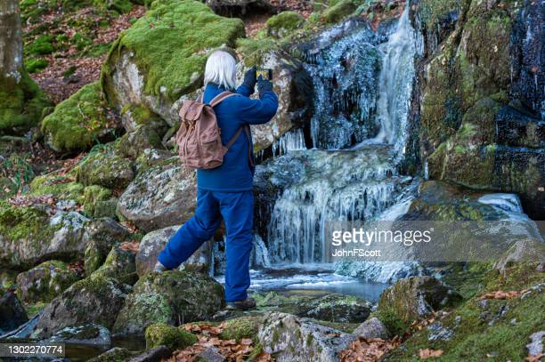 retired man taking a photo of a frozen waterfall - johnfscott stock pictures, royalty-free photos & images