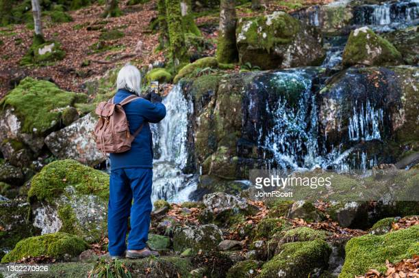 retired man taking a photograph of a frozen waterfall - johnfscott stock pictures, royalty-free photos & images
