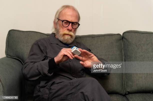 retired man using an oximeter to check the oxygen level in his blood - johnfscott stock pictures, royalty-free photos & images