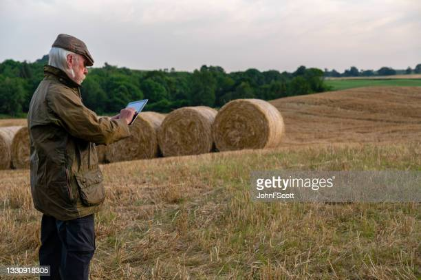retired man using digital tablet after a harvest - johnfscott stock pictures, royalty-free photos & images