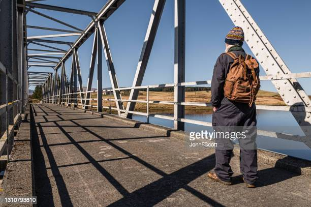 retired man walking across a steel bridge - johnfscott stock pictures, royalty-free photos & images