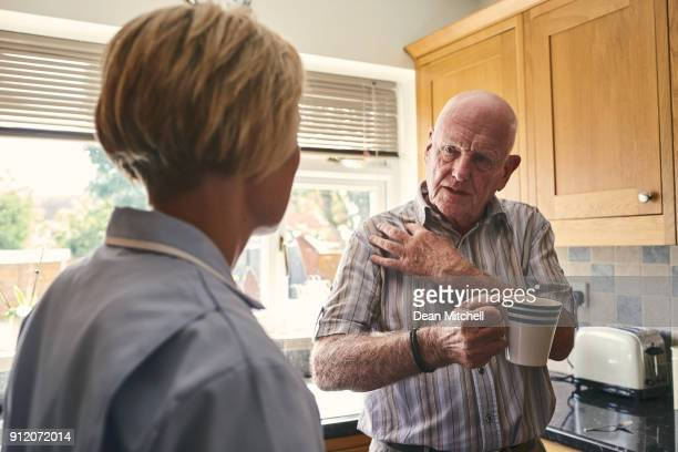 retired man with aching shoulder talking to home carer - shoulder stock pictures, royalty-free photos & images
