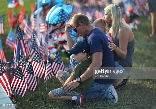 Retired Marine Michael Hendon Logan Hendon and Mandy Hendon pay their respect at a memorial setup in front of the Armed Forces Career Center/National...