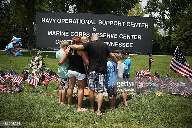 Retired Marine Veteran Brandon Hetrick prays with his family at a memorial setup at the entrance to the Navy Operational Support Center and Marine...