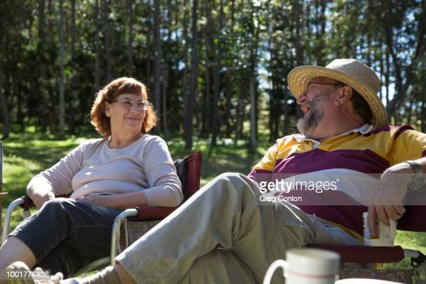 Retired married couple having morning tea, laughing and discussing life in the outdoors