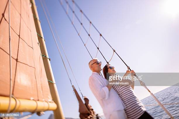 Retired mature couple on yacht with ocean and blue sky