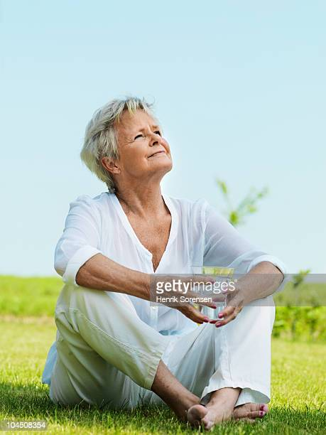 retired mature woman sitting with glass of water - hillerod stock pictures, royalty-free photos & images